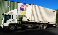 Tilt tray truck unloading a container